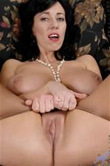 Busty nude cougar plays with her wet shaved pussy on the sofa till she ...